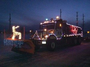 A plow truck covered in holiday lights drives down the road