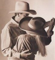 A couple in cowboy hats dance together